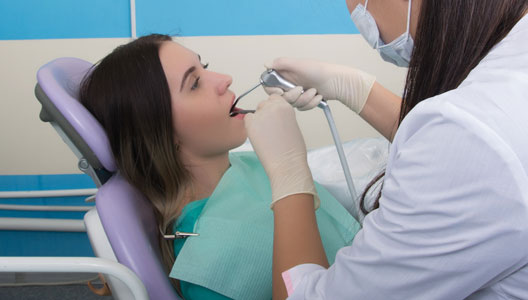 Girl patient lying in a chair opening her mouth wide showing her teeth to Doctor for whitening procedure at 4 square dentistry.