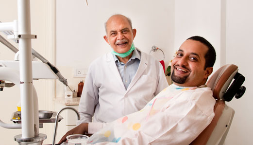 Dentist at 4SquareDentistry checking teeth and gums for damage due to Periodontitis