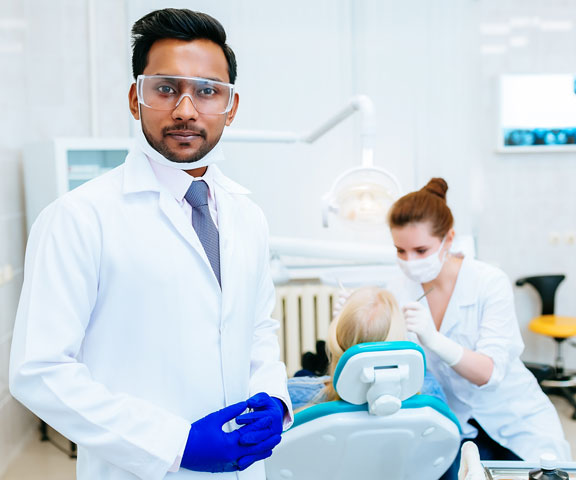 A smiling lady dentist in front of her workstation at 4SquareDentistry